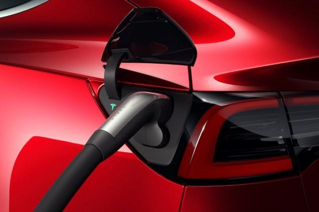 Tesla-Model-3-am CCS Supercharger Ladeanschluss an rotem Elektroauto