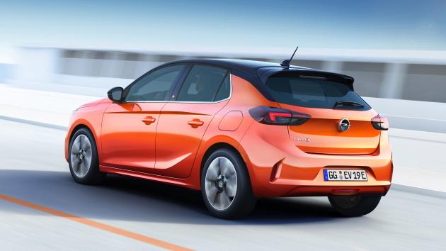 Opel Corsa-e orange heck hinten auf straße fahrend